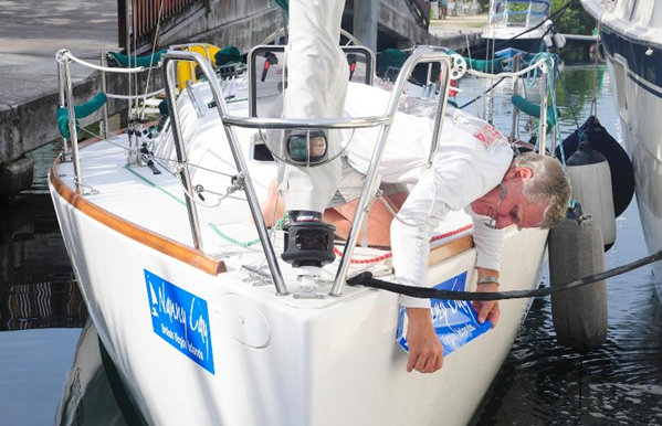 Regatta bow stickers are carefully applied. Ready to race!  Credit: Todd vanSickle/BVI Spring Regatta & Sailing Festival
