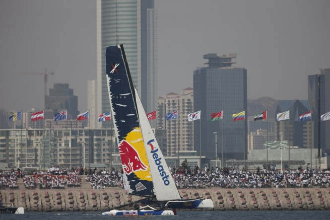 Red Bull Sailing Team flying a hull in front of spectators lining the breakwater in Fushan Bay, Qingdao