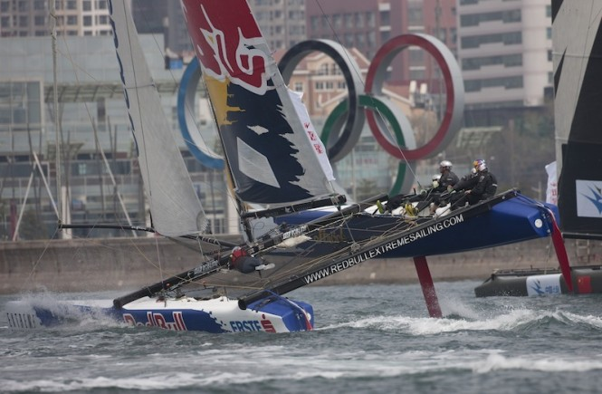 Red Bull Sailing Team flying a hull in front of the Olympic rings - Photo Lloyds Images