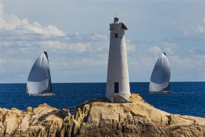 Luxury yachts Shockwave and Ran approach the lighthouse at Monaci - Photo by Rolex Carlo Borlenghi