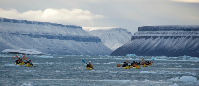 Members of EYOS Expeditions kayaking amidst beautiful Arctic scenery
