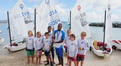 Thad Lettsome (left side of baton); Glenford Gordon (holding baton) and local optimist sailors with the Queen's Baton Credit: Todd vanSickle/BVI Spring Regatta
