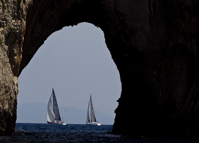 Competitors pass by the Faraglioni Rock formations off the south-east coast of Capri - Image by Rolex Carlo Borlenghi