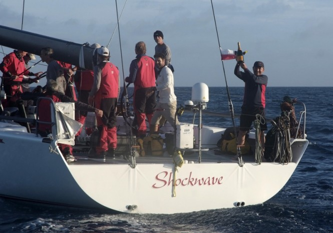 Owner of Shockwave Yacht, George Sakellaris, waving a victory bottle of champagne - Photo by Barry Pickthall