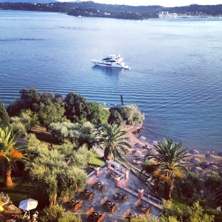 The 75 Yacht FINEZZA pictured in the morning of the event, with beautifully still waters and the stunning Corfu Imperial Hotel nearby