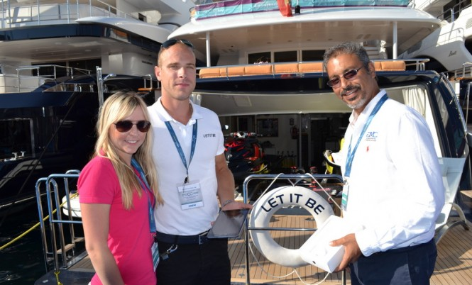Costas from GMC and Michelle from Yachting Pages handing an iPad mini to Lucas from motor yacht Let it Be