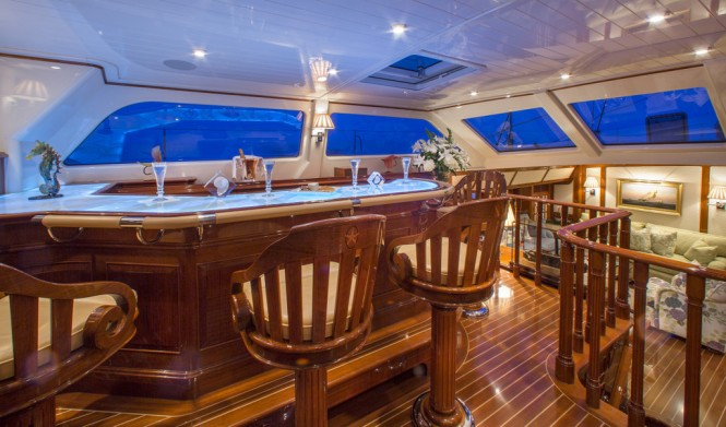 Whisper's teak interior is adorned with intricate inlays and carvings and includes an upper pilothouse lounge (left) that boasts a full wet bar with panoramic views of the horizon