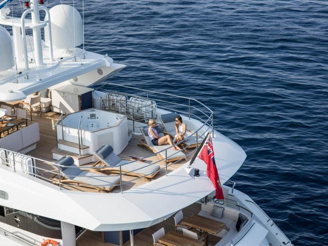 The aft sundeck Jacuzzi and sun loungers aboard superyacht FLEUR