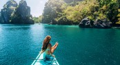 Back view of the young girl relaxing on the boat and looking at