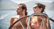 Beautiful couple on sailboat, young happy family behind helm of