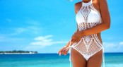Beautiful woman wearing crochet bikini posing over the sea view,