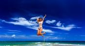 Model In White Bikini Jumping At The Beach