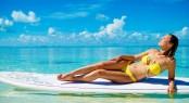 Woman in bikini sunbathing on the paddle board in Exuma, Bahamas