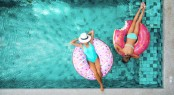 Two people (mom and child) relaxing on donut lilo in the pool at
