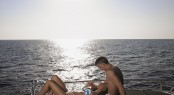 Loving couple relaxing at the edge of yacht by sea