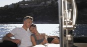 Romantic couple having champagne while sitting at table on yacht