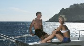 Side view of woman sitting on yacht with man standing in backgro