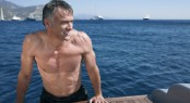 Middle aged man looking away while leaning on the edge of yacht'
