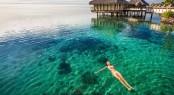 Woman in white bikini swimming in coral lagoon at the resort, Mo