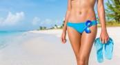 Sexy bikini body woman - abs, sunglasses, flip flops on beach va