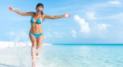 Sexy bikini body woman playful on paradise tropical beach having