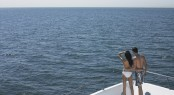 Rear view of young couple standing on bow of yacht looking at se