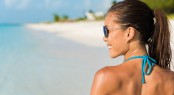 Happy beach lifestyle sunglasses girl smiling having fun. Beauti