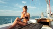 Young beautiful brunette girl drinking cocktail while resting on