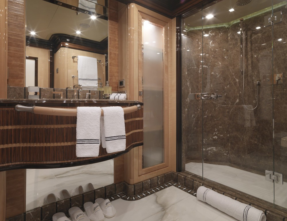 ensuite bathroom with marble walls and flooring and built-in luxury furniture