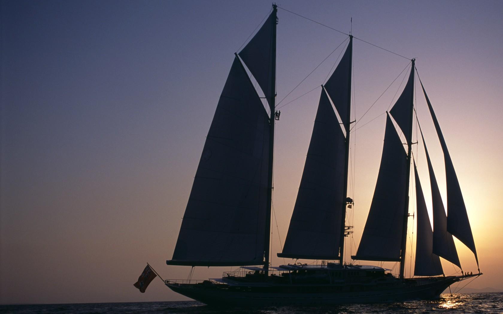 90m Royal Huisman sailing mega yacht at sunset