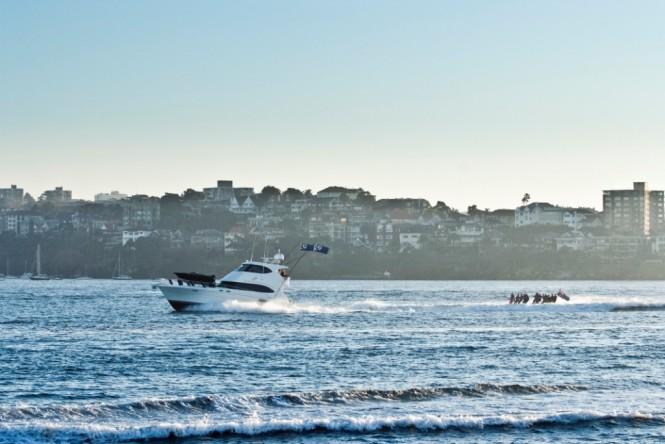 Riviera 61 series II Enclosed Flybridge luxury motor yacht and waterskiers in Sydney Harbour