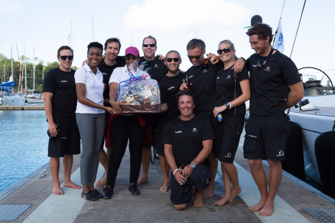 Overall winners and first recipients of the RORC Transatlantic Race Trophy as well as the IMA Trophy for Line Honours - charter yacht Lupa of London's crew enjoy a warm Grenadian welcome and a huge basket of local goodies on arrival