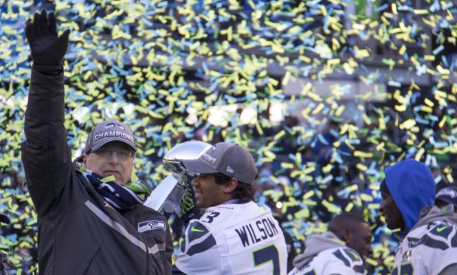 Paul Allen waves to the 12s during the Super Bowl parade and rally at Seattle's CenturyLink Field in February 2014. Credit Courtesy of Vulcan Inc.