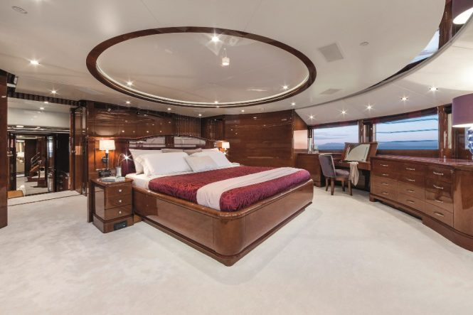 Spacious master stateroom with plush furnishings and elegant wooden furniture