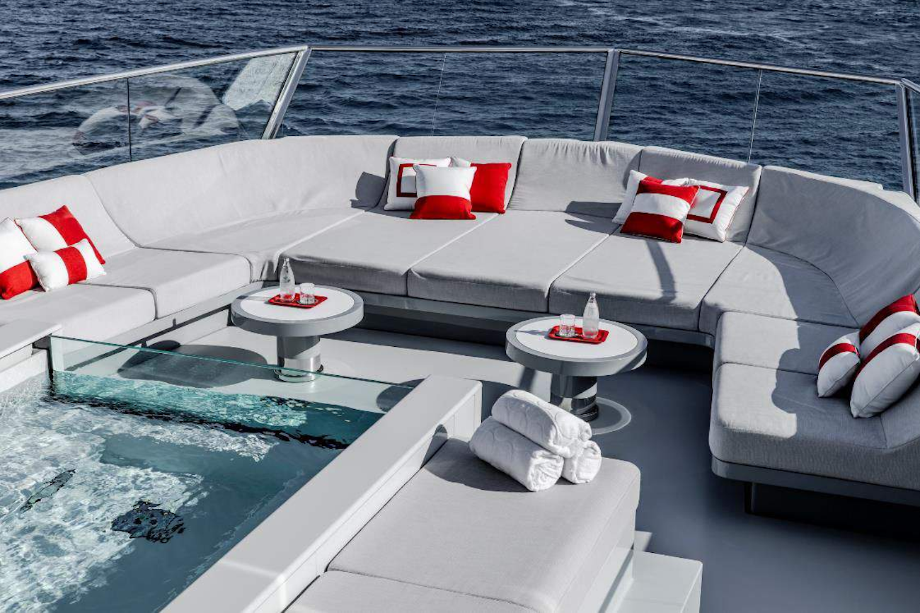 Large 8-person Jacuzzi surrounded by comfortable seating and sun loungers